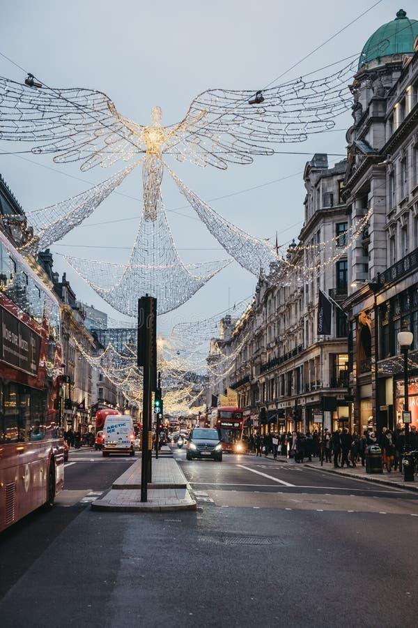 Autobus, voitures et piétons sous des lumières de Noël d'ange sur Regent Street, Londres, R-U photographie stock libre de droits