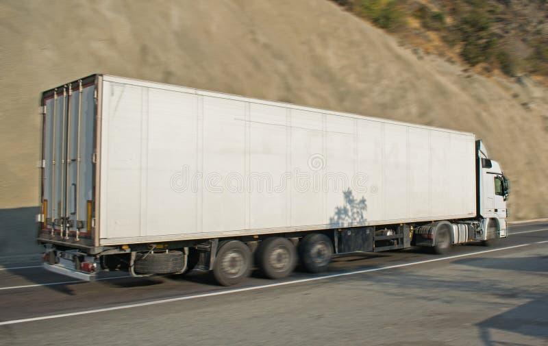 Autocarri che trasportano merci su strada, in movimento Panning Nessun logo immagine stock libera da diritti