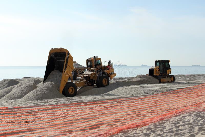 Autocarri con cassone ribaltabile che riempiono la sabbia della spiaggia immagini stock