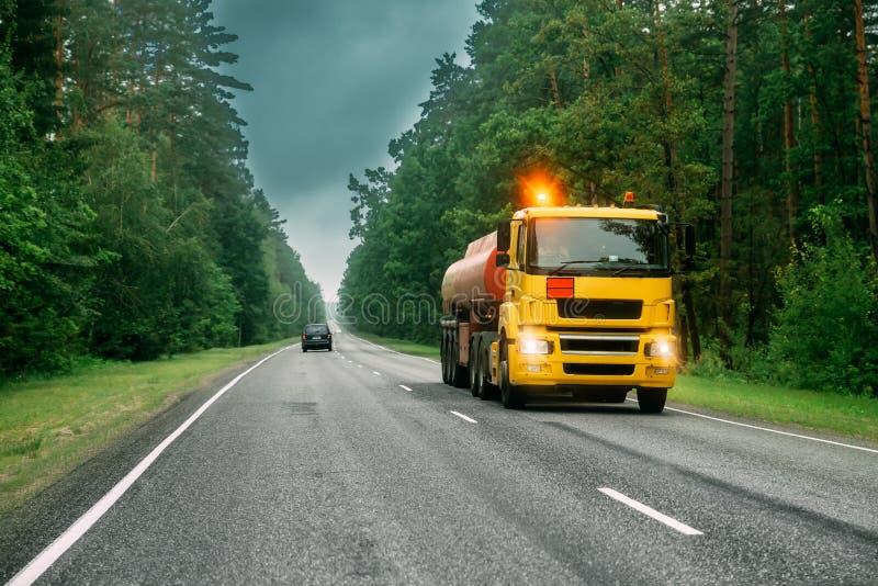 Autocisterna o camion cisterna, trasportante benzina sulla strada campestre fotografia stock libera da diritti
