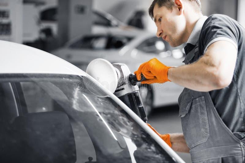 Autodetails - ein männlicher Arbeiter hält einen Polierer in der Hand und poliert weißes Auto in der Autowerkstatt stockfoto