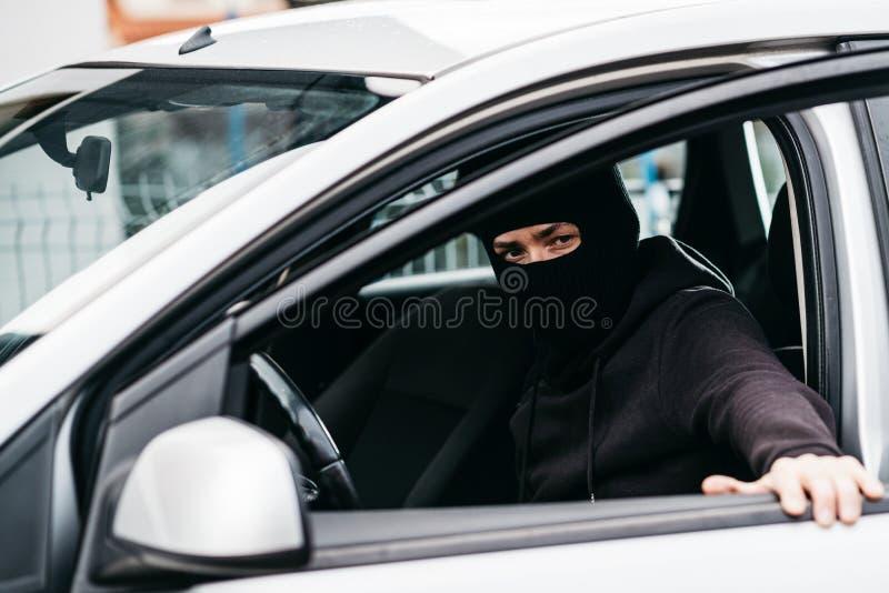Autodief in zwarte balaclava sluitende deur van gestolen auto royalty-vrije stock afbeelding