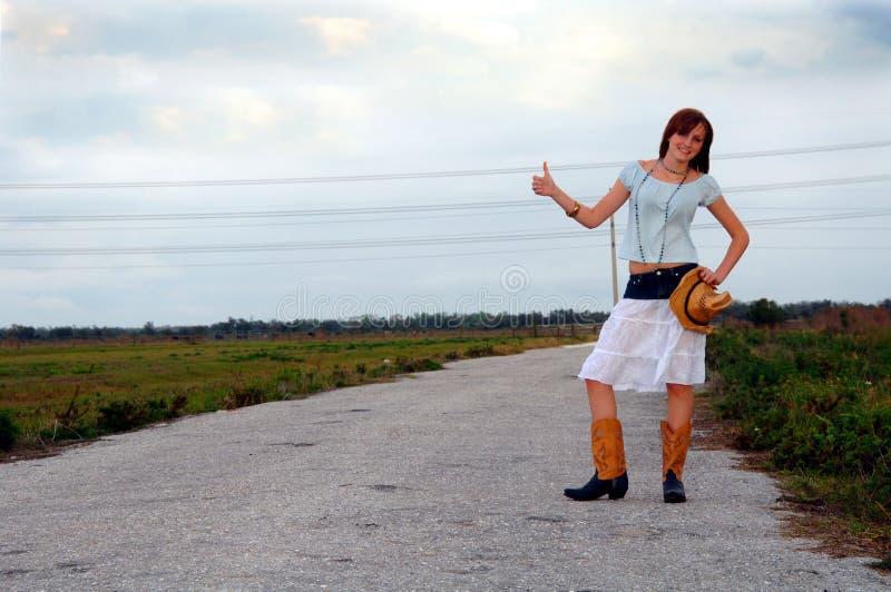 Autoestop de la muchacha del país en el camino rural fotos de archivo libres de regalías