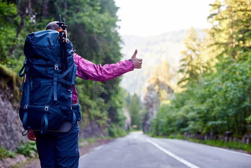 Autoestop turístico de la mujer en el camino vacío de la montaña rodeado por las colinas rocosas herbosas en Rumania fotos de archivo libres de regalías