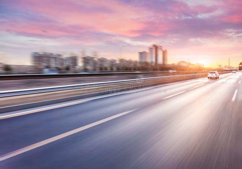 Autofahren auf Autobahn bei Sonnenuntergang, Bewegungsunschärfe stockfotos