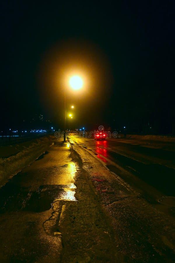 Autofahren entlang eine Nachtstraße beleuchtet durch Laternen lizenzfreies stockbild