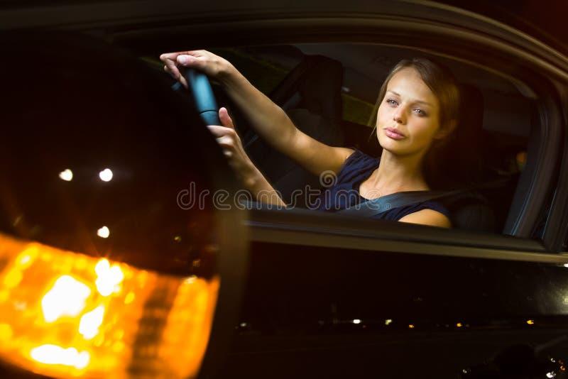Autofahren nachts - recht, junge Frau, die ihr Auto fährt stockbilder
