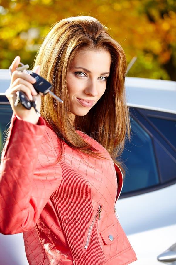 Autofahrerfrau, die Neuwagenschlüssel und -auto zeigt. stockbild