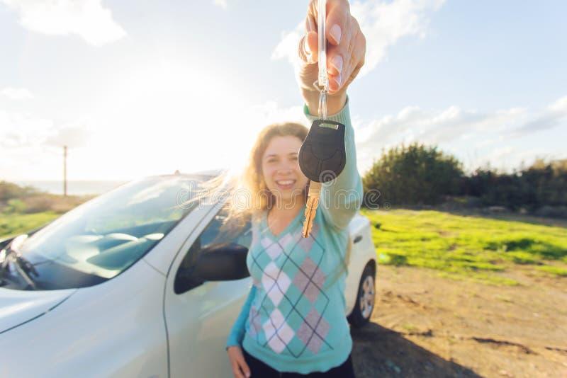 Autogeschäft, Autoverkauf, Verbraucherschutzbewegung und Leutekonzept - glückliche Frau, die NeuwagenSchlüsselim Freien hält lizenzfreies stockfoto