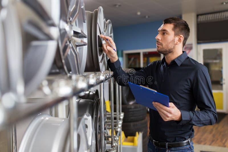 Autogeschäftinhaber und -Radfelgen am Autoservice lizenzfreie stockfotos