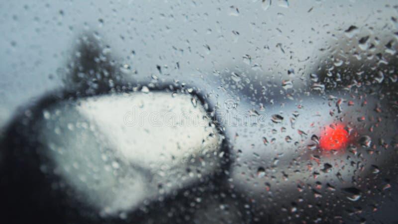 Autoglas an einem regnerischen Tag - defocused Hintergrund Bewegliche waterdrops in den Wischern der Windschutzscheibe lizenzfreies stockfoto