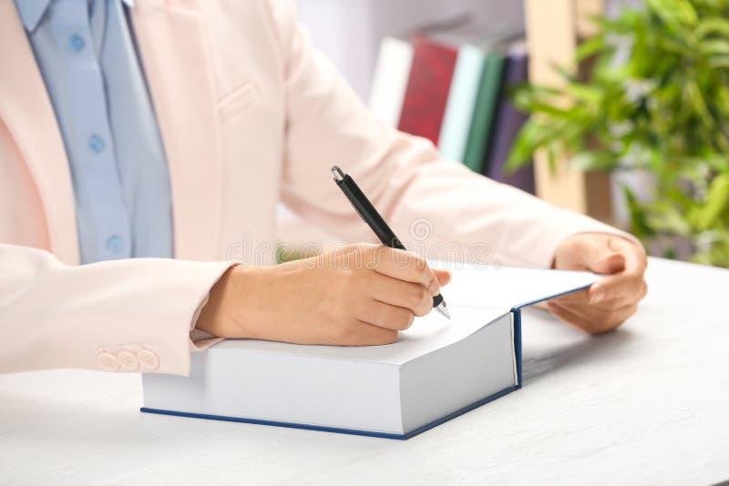 Autografo di firma dello scrittore in libro a tabl immagini stock