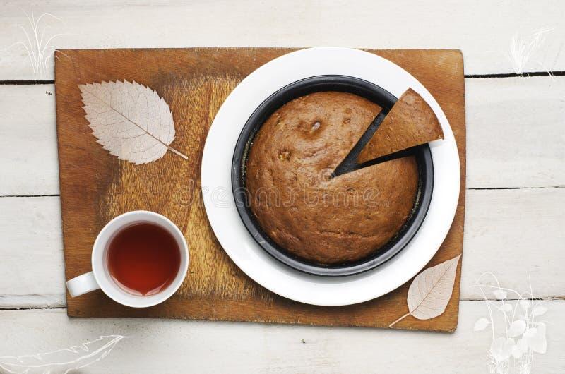 Autoguidez fait la banane pour durcir avec la tasse de thé sur le fond blanc Gâteau en tant qu'homme de paquet (jeu d'ordinateur  photos stock