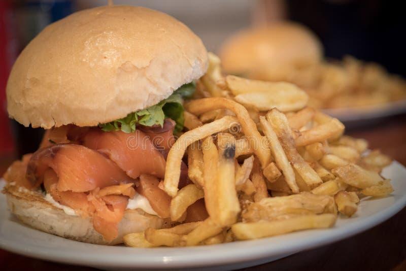 Autoguidez l'hamburger saumoné fait avec des pommes frites placées sur le plat blanc photos libres de droits
