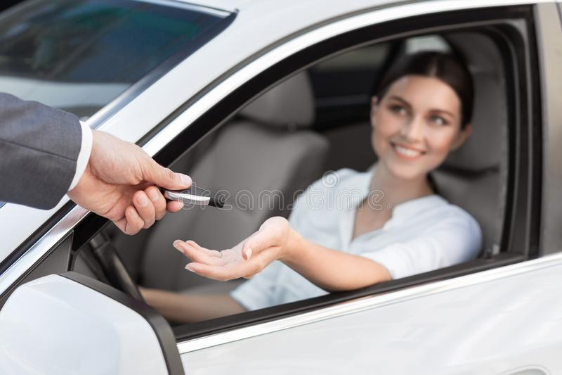 Autohändler, der dem glücklichen weiblichen Kunden Schlüssel gibt stockfotografie