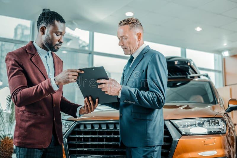 Autohandelaar die een contract met de cliënt besluiten royalty-vrije stock foto