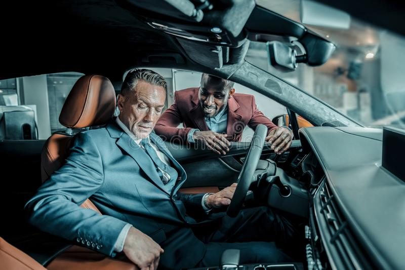 Autohandelaar die zijn cliënt vragen over de indrukken royalty-vrije stock afbeelding