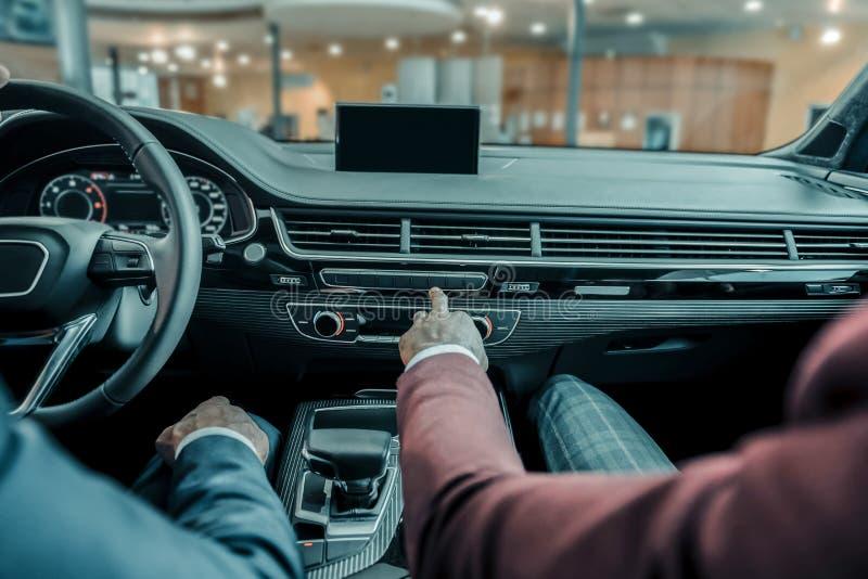 Autohandelaar die zijn cliëntfuncties van de auto tonen stock afbeelding