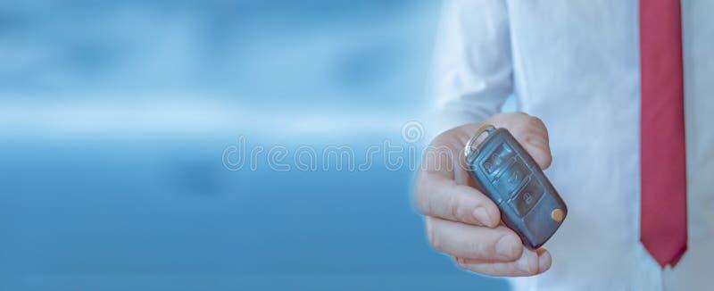 Autohandelaar met een sleutel Auto het handel drijven en huurconceptenachtergrond stock afbeeldingen