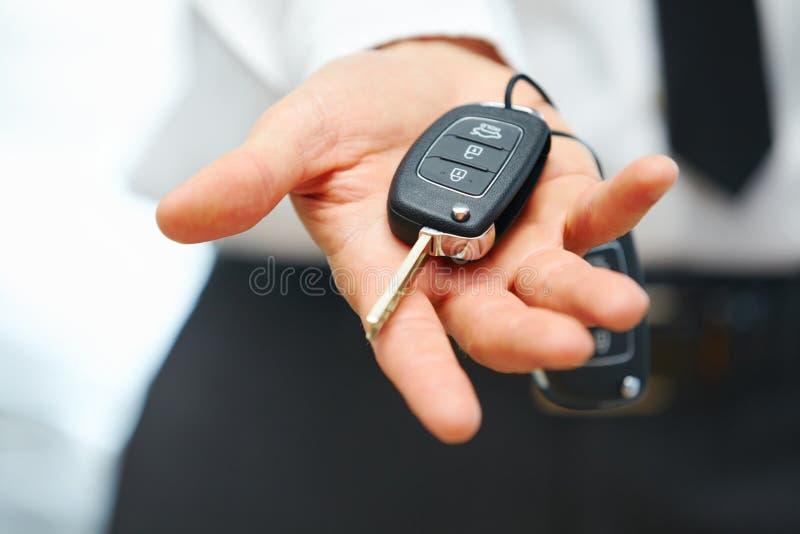 Autohaus- und Mietkonzepthintergrund Verkäuferhand, die Schlüssel gibt stockbild