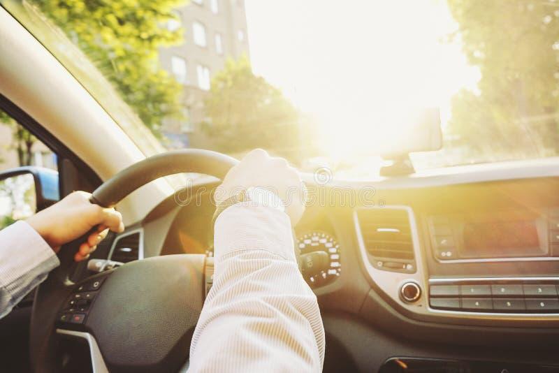 Autoinnenraum mit dem männlichen Fahrer, der hinter dem Rad, weiches Sonnenunterganglicht sitzt Luxuriöser Fahrzeugarmaturenbrett lizenzfreie stockfotos