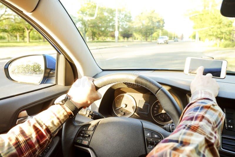 Autoinnenraum mit dem männlichen Fahrer, der hinter dem Rad, weiches Sonnenunterganglicht sitzt Luxuriöser Fahrzeugarmaturenbrett stockbilder