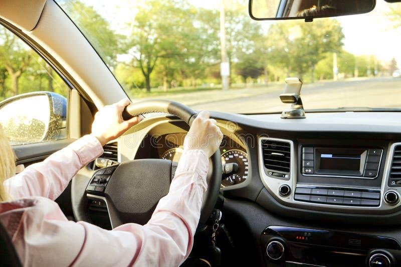 Autoinnenraum mit dem weiblichen Fahrer, der hinter dem Rad, weiches Sonnenunterganglicht sitzt Luxuriöser Fahrzeugarmaturenbrett stockbild