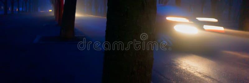 Autokoplampen in de avond op een stadsstraat, vage achtergrond stock afbeelding