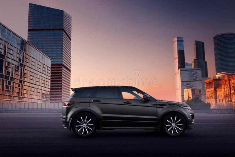 Autoland Rover Range Rover Evoque die zich op asfaltweg in stad Moskou bij zonsondergang bevinden stock afbeelding