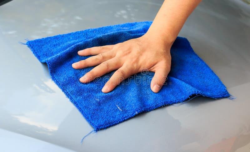 Autolavaggio senz'acqua Mano del ` s degli uomini con l'automobile blu di pulizia del panno fotografia stock