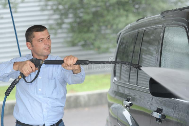 Autolavaggio - uomo che lavora con la rondella ad alta pressione fotografia stock libera da diritti