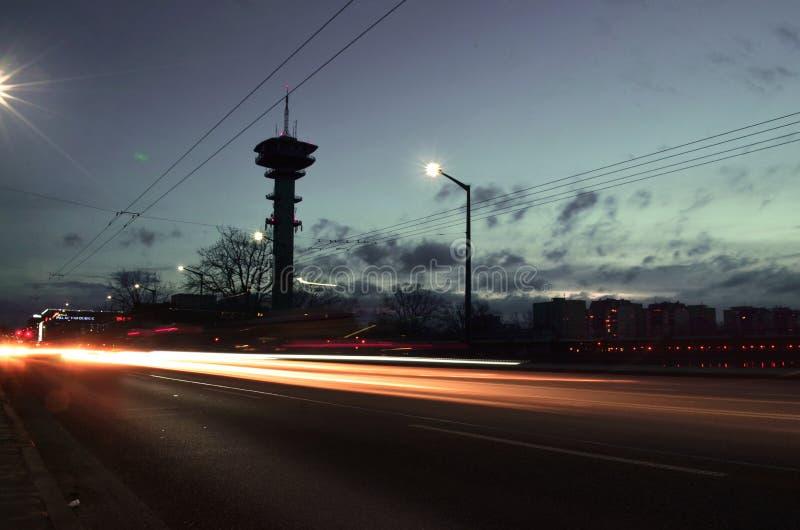 Autolichten en zonsondergang in Europese stad stock afbeelding