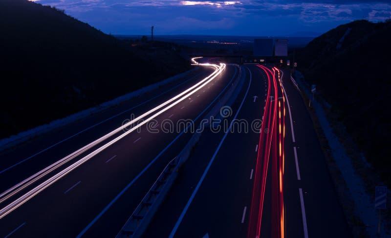 Autolichter auf Landstraße stockbilder