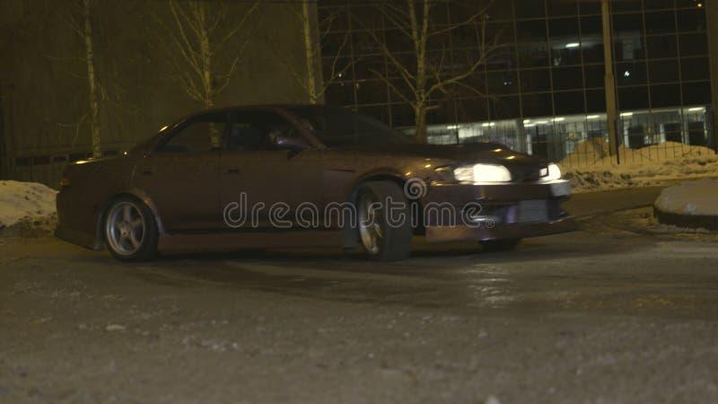 Automóvel de passageiros roxo bonito que deriva nas ruas da cidade na noite na estação do inverno a??o Um carro que entra em um p foto de stock royalty free