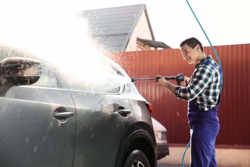 Automóvil de la limpieza del trabajador con el chorro de agua de alta presión imágenes de archivo libres de regalías