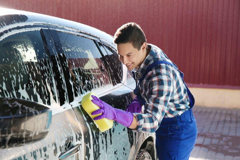 Automóvil de la limpieza del trabajador con la esponja imagen de archivo libre de regalías