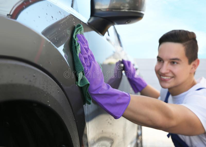 Automóvil masculino de la limpieza del trabajador con el trapo foto de archivo libre de regalías