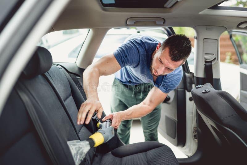 automóvil que limpia con la aspiradora y de limpieza del trabajador Mantenimiento del coche y concepto de detalle foto de archivo