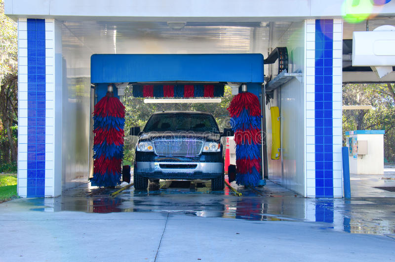 Automated car wash with a soapy truck. An automated car wash facility with a soapy truck in the process of getting washed stock photography