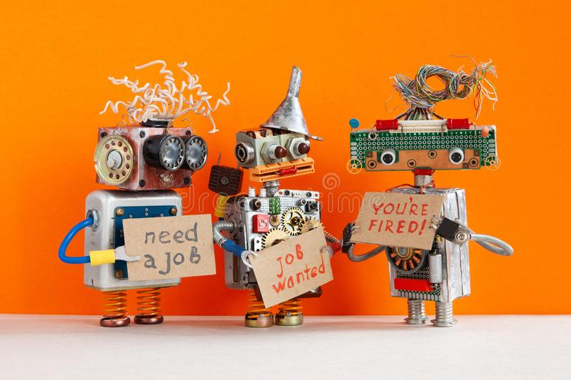 Automated dismissal and hiring of staff. The relationship between employer and employee. robot boss dismisses personnel. And shows cardboard You are fired. Two stock photography