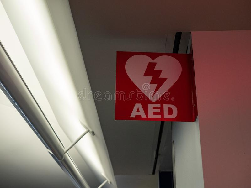 Automated external defibrillator AED logo hanging in public area. Automated external defibrillator AED logo and sign hanging in public area stock photos