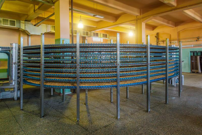 Automated round multilevel conveyor machine in bakery food factory, cookies and cakes production line royalty free stock images