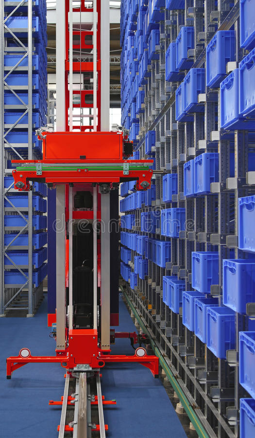 Automated storage robot. Automated storage warehouse with blue plastic crates royalty free stock images