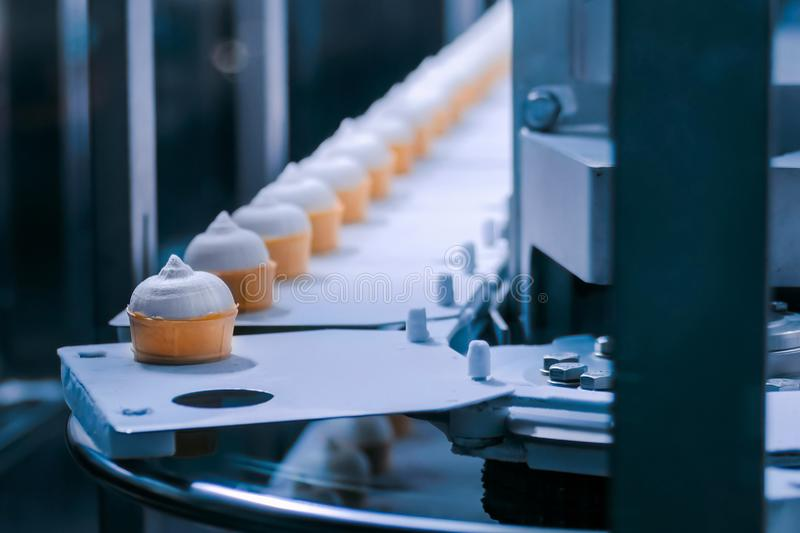 Automated technology concept - conveyor belt with icecream cones at food factory stock photo