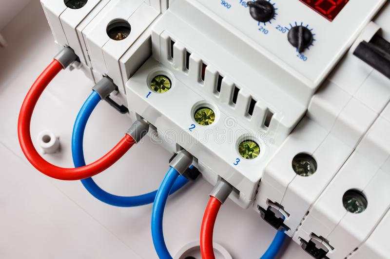 Automatic circuit breakers and voltage limiter connected by red and blue wires closeup in the white plastic mounting box stock photography
