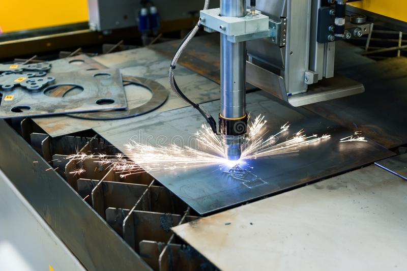 Automatic CNC plasma cutting machine cuts details from steel sheet. stock photo