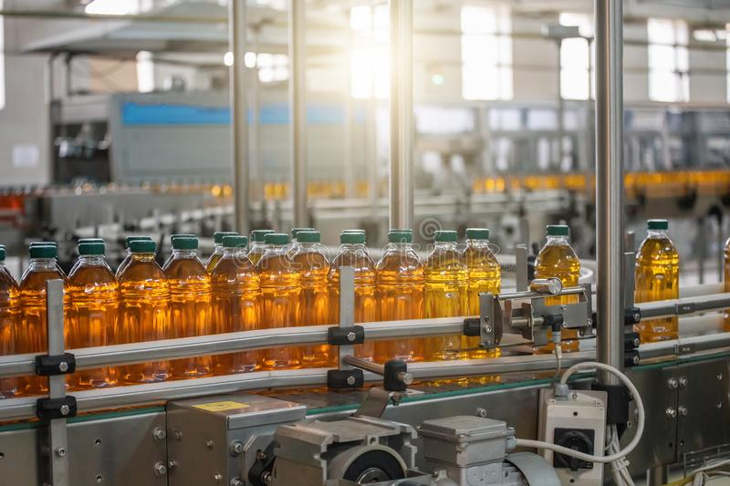 Automatic conveyor belt of production line of juice on beverage plant or factory, modern computerized industrial equipment. Fresh juice in plastic bottles royalty free stock images