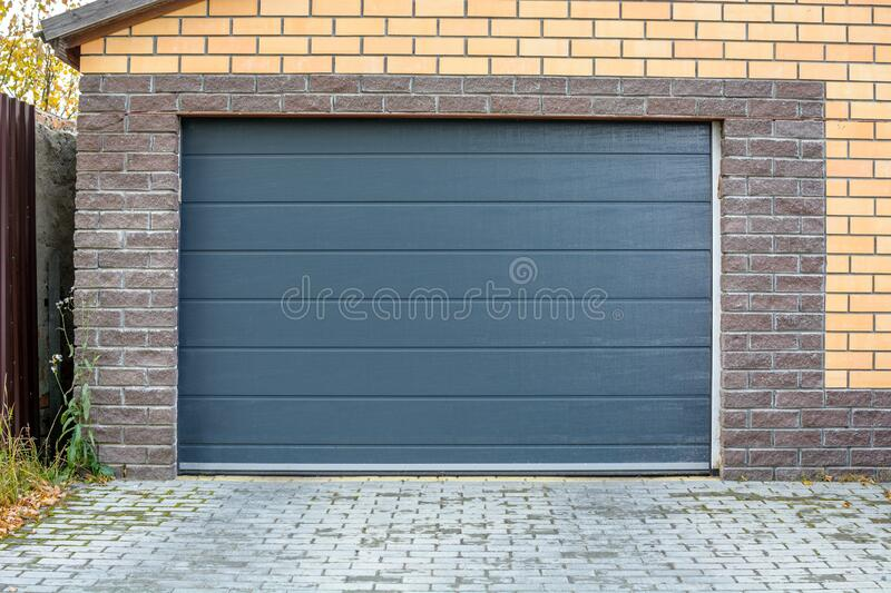 Automatic garage gate. Access to a garage for a car with a dark door. Automatic garage gate. Access to a brick garage for a car with a dark door royalty free stock image
