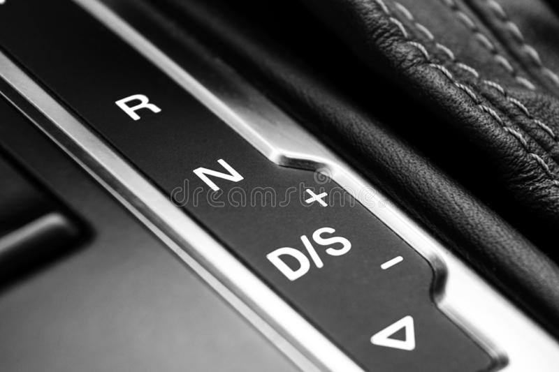 Automatic gear stick of a modern car. Modern car interior details. Close up view. Car detailing. Automatic transmission lever stic. K shift. Black and white royalty free stock photo