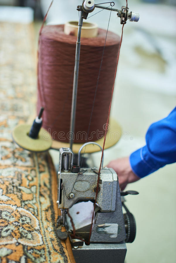 Automatic industrial sewing machine for hemming carpets. In dry cleaning stock photo